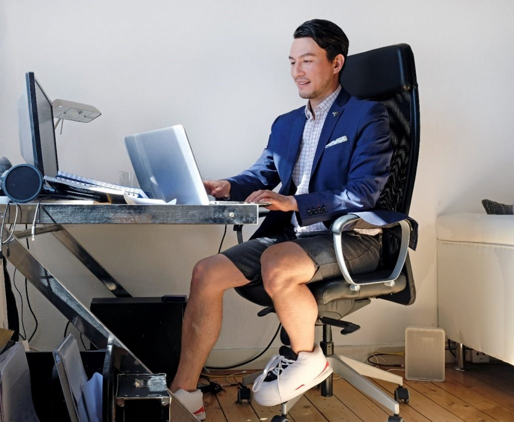 Man working at home wearing a shirt and blazer on the top half, shorts and trainers below the desk.